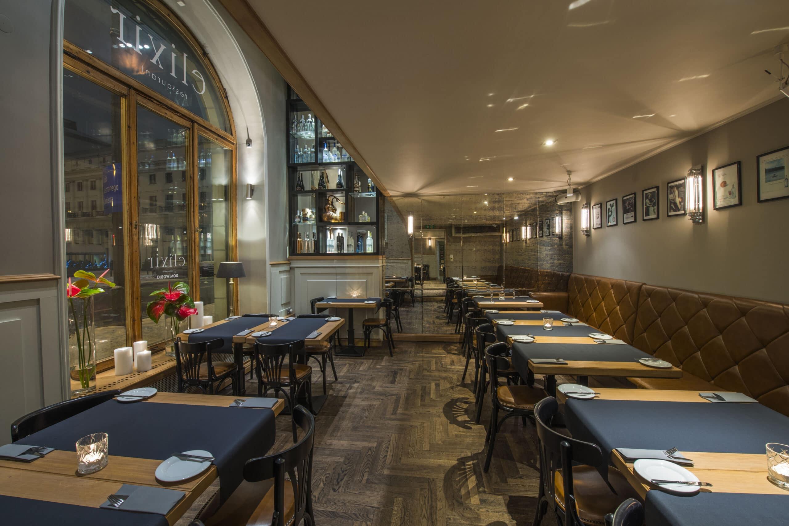 wnętrze restauracji z nakrytymi stołami, w tle regał z alkoholem