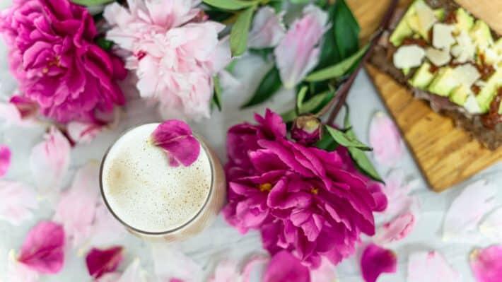 kawa na stole przy różowych kwiatach