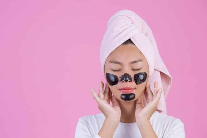 kobieta usuwa wągry z nosa i twarzy