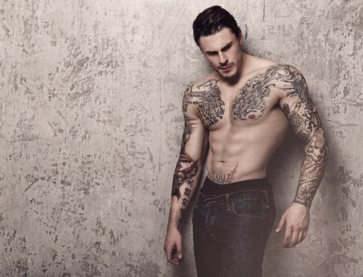 Silny mężczyzna w tatuażach oznaczających odwagę