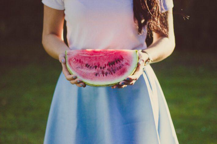 Kobieta w niebeiskiej sukience i białej bluzce, trzymająca w rękach arbuz i cennych wartościach odżywczych