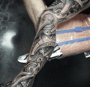 Dziara na nodze w formie tatuażu biomechanicznego