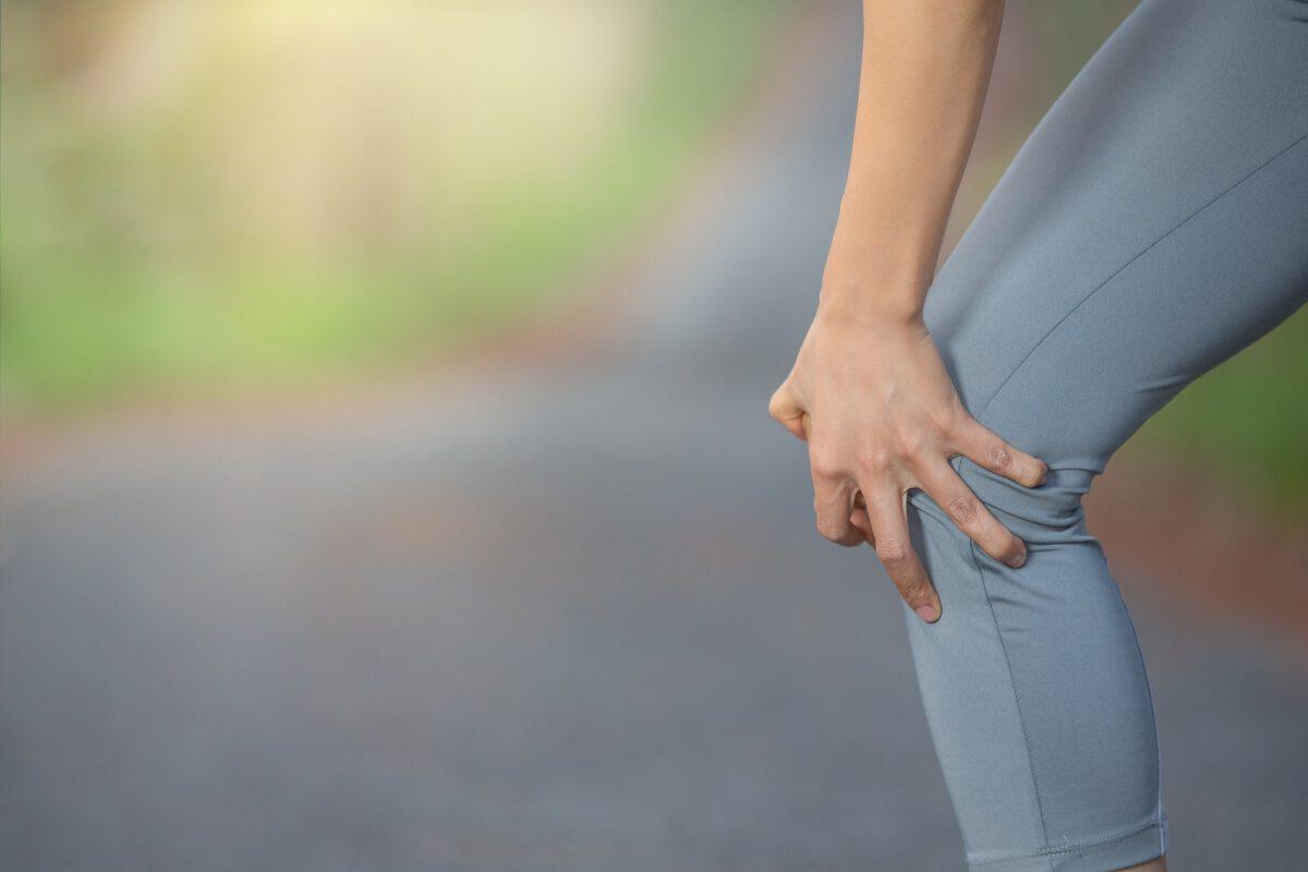 Biegaczka trzymająca się za bolące kolano po bieganiu