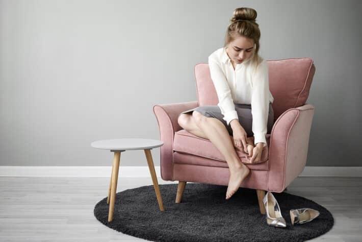 Kobieta siedząca na fotelu i masująca swoje bolące stopy