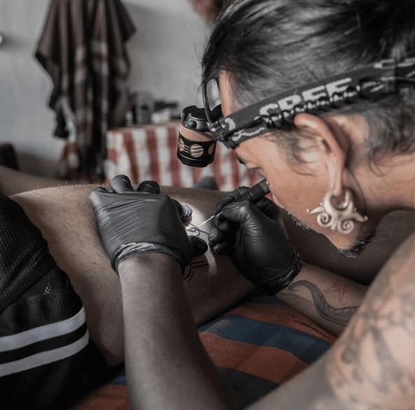 Mężczyzna robiący hand poked tattoo