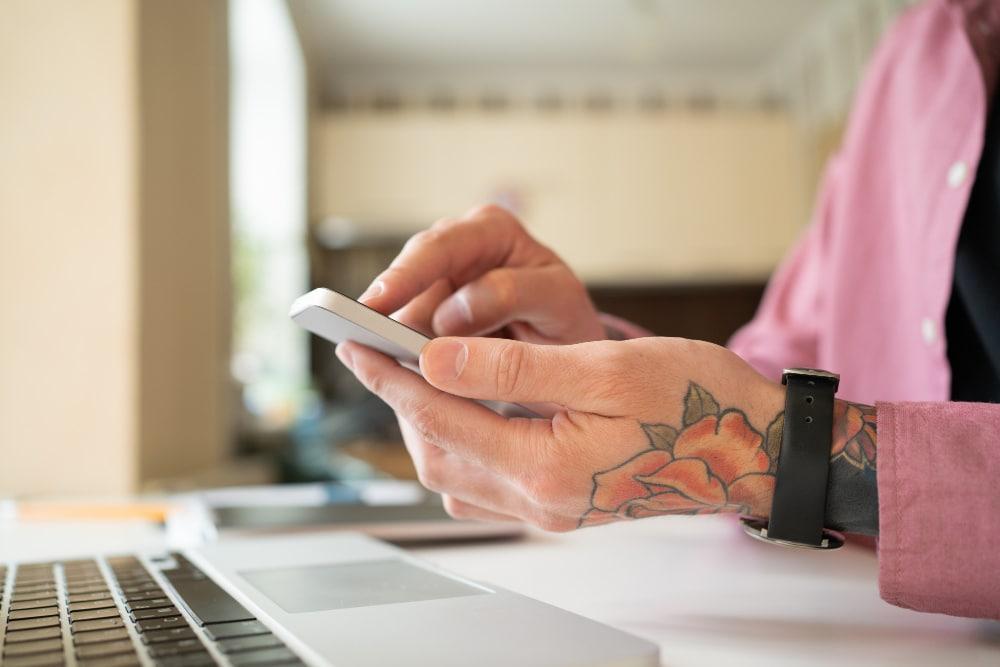 Kobieta trzymająca telefonw rękach, mająca tatuaż różę na dłoni