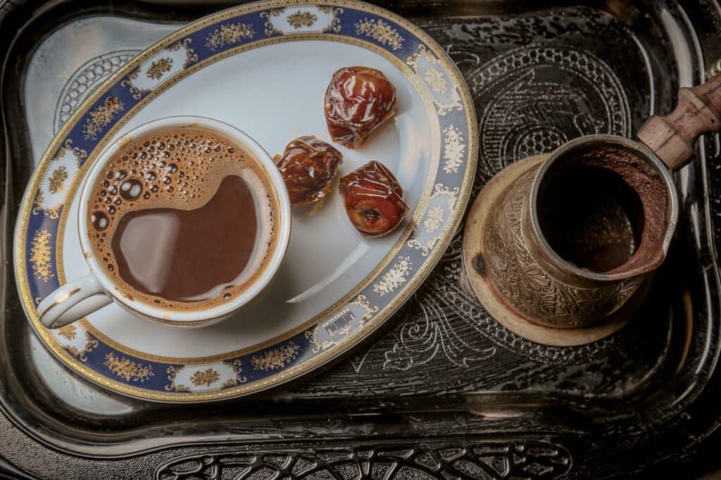 Daktyle na talerzyku podawane z czarną kawą