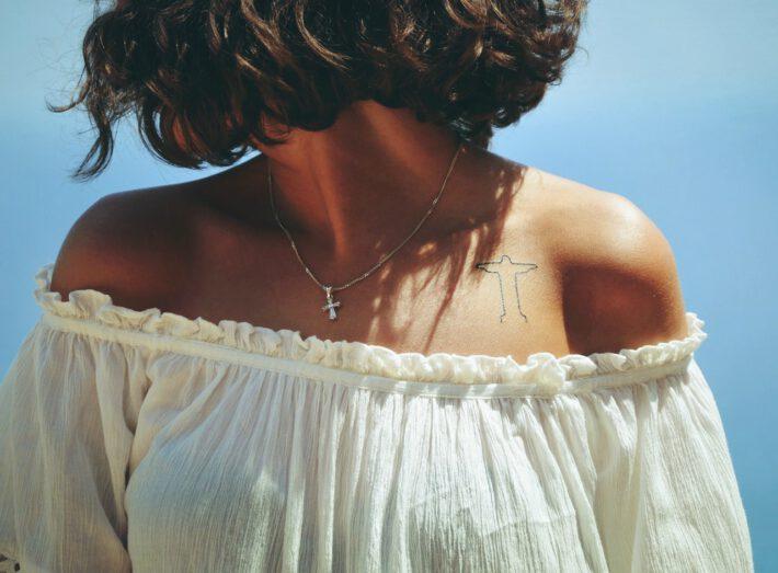 Młoda kobieta w jasnej koszulce mająca tatuaż krzyż na ciele