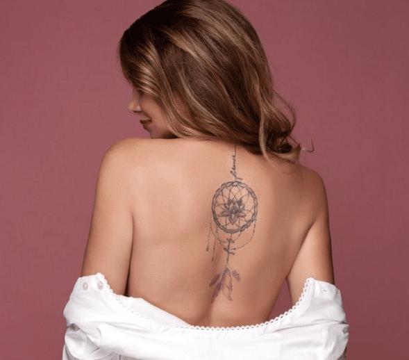 Kobieta mająca na plecach tatuaż łapacz snów