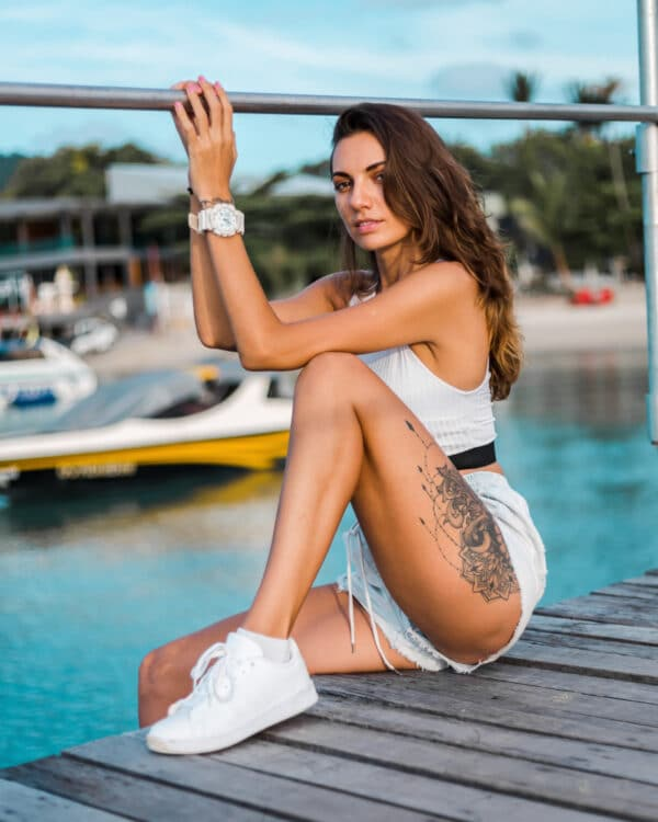Młoda kobieta siedząca na pomoście nad wodą, z tatuażem na nodze