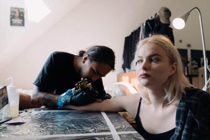 Kobieta robiąca tatuaż, u której może wystąpić uczulenie po tatuażu