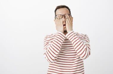 Portret stojącego mężczyzny pocierającego oczy, które nieustannie go bolą