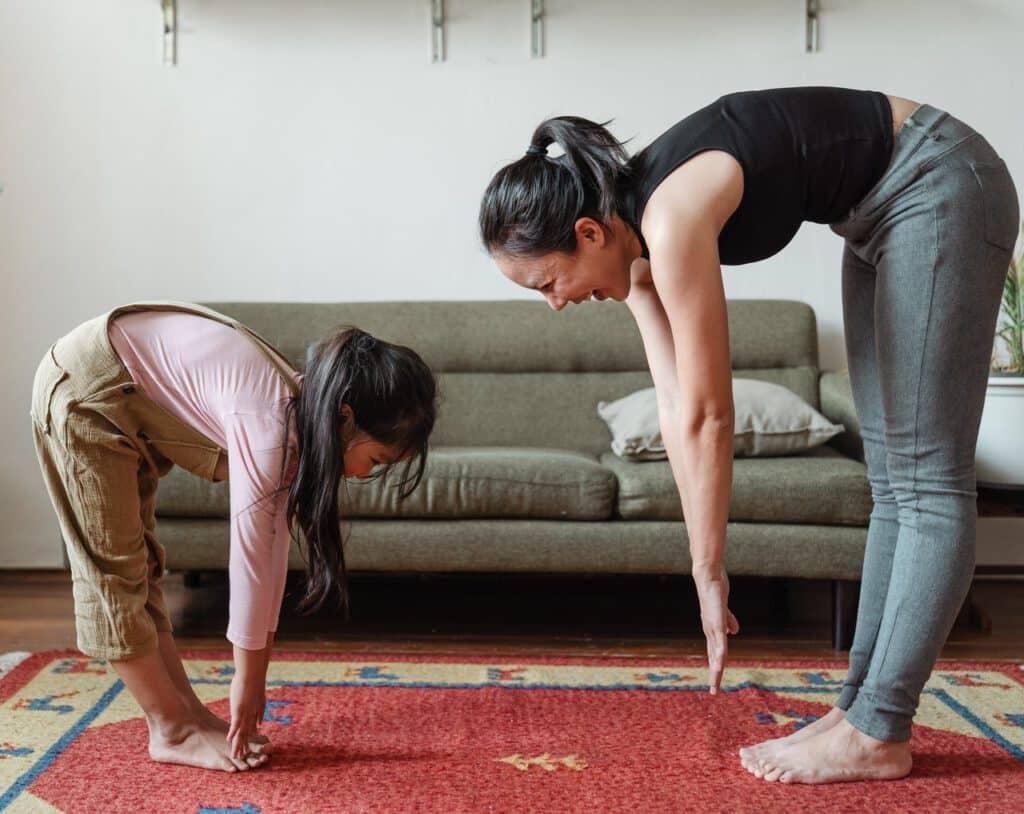 Mama z córką wykonująca ćwiczenia na uda i pośladki w domu