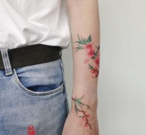 Kobieta z tatuażem kwiat wiśni na ręce