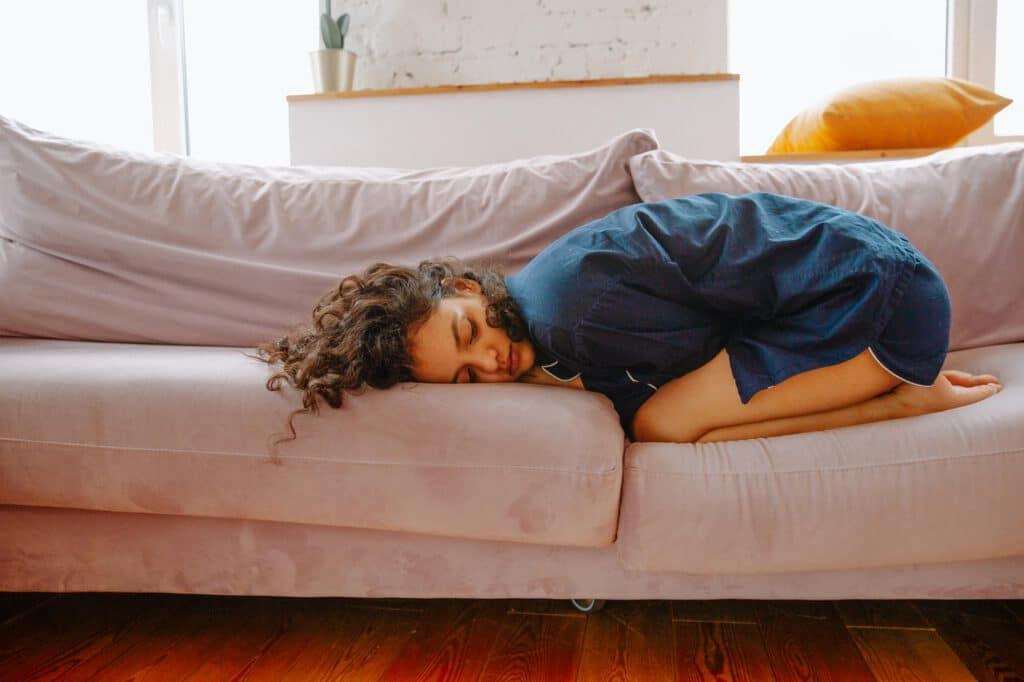 Leżąca na kanapie kobieta z bólem jajników