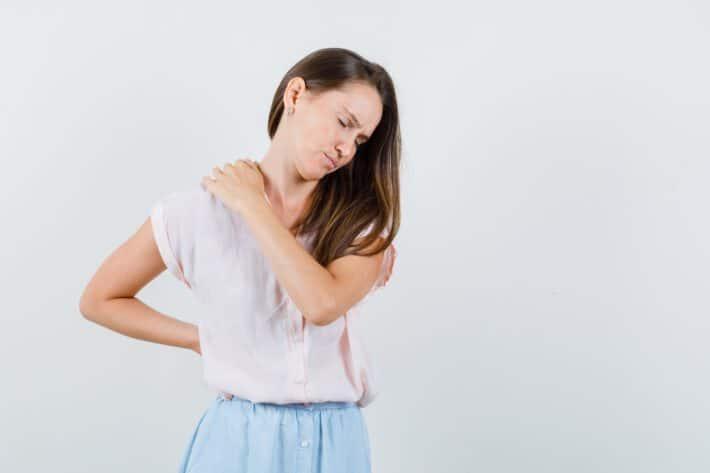Kobieta o nieprzyjemnym grymasie twarzy, świadczącym o bólu pleców między łopatkami