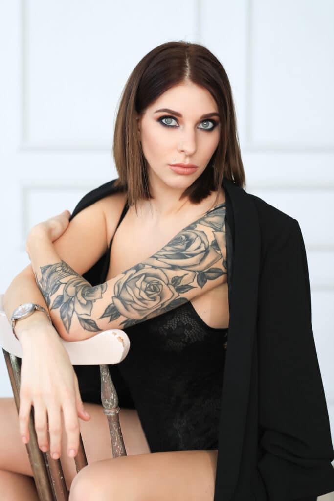 Młoda kobieta z tatuażami róża na ręce
