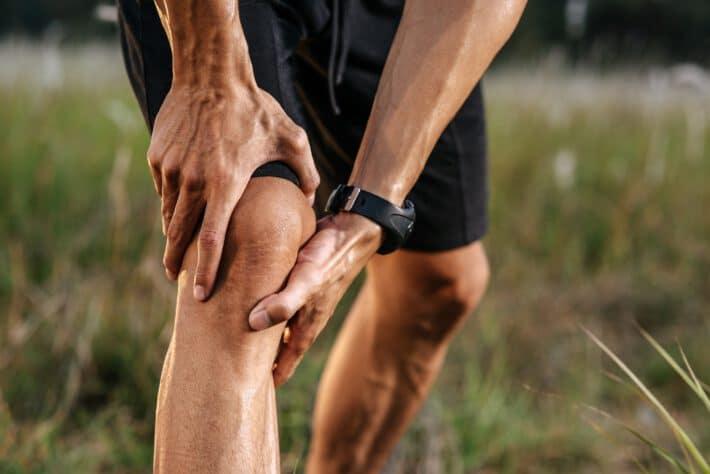 Mężczyzna pochylający głowę łapiący się po bieganiu za bolące kolano