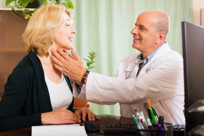 Lekarz badający kobietę pod kątem powiększonej tarczycy