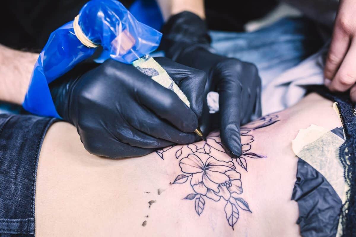 Kobieta w salonie tatuażu wykonująca tatuaz kwiaty