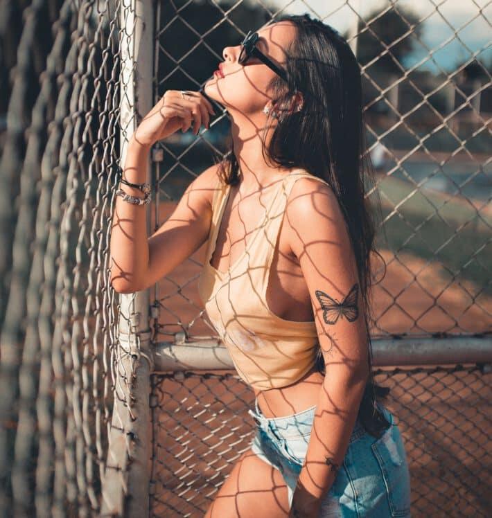 Młoda kobieta z tatuażem motylem na ręce