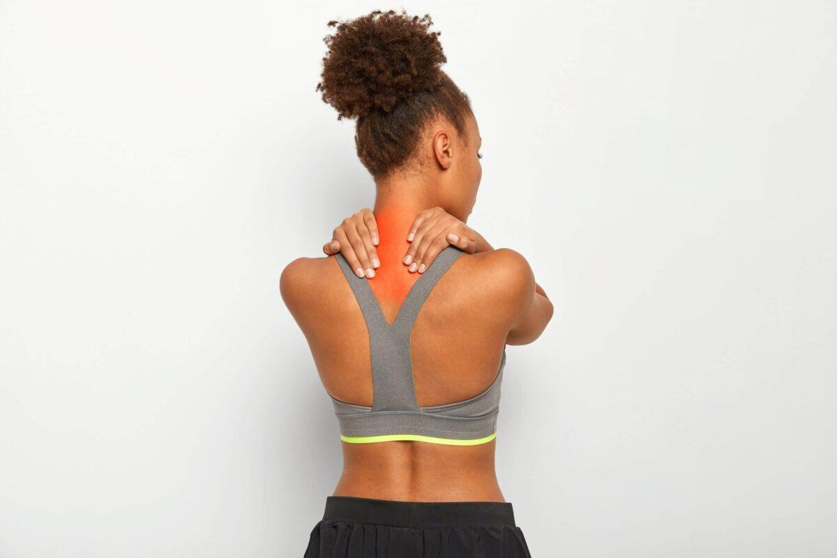 Młoda kobieta trzymająca się za szyję, cierpiąca na ból pleców