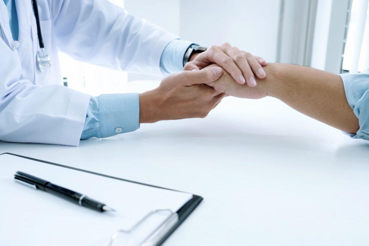 Lekarz trzymający pacjenta za rękę, który poddawany jest leczeniu paliatywnmu