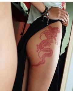 Kobieta przeglądająca sie w lustrze i eksponująca swój czerwony tatuaz na biodrze