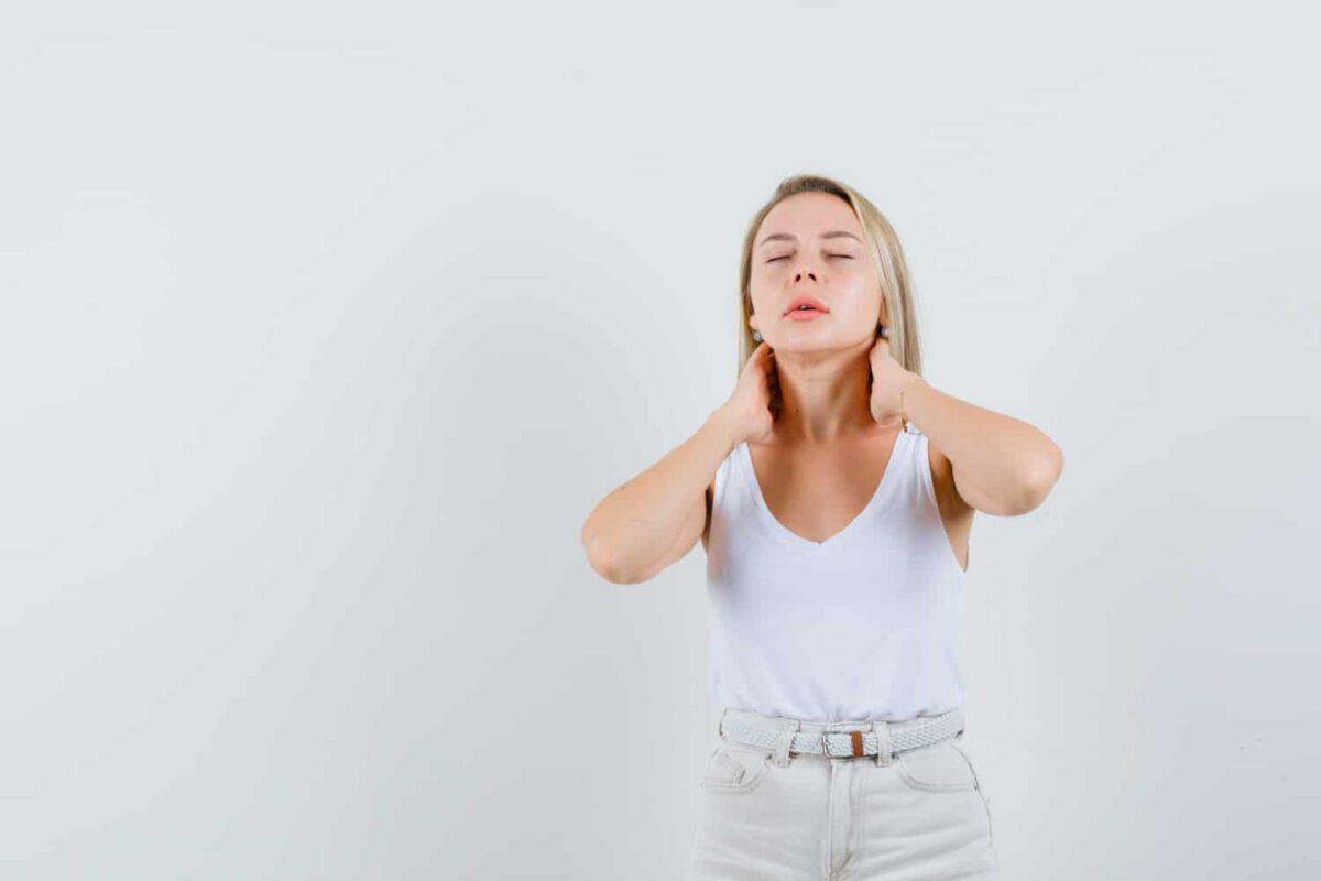 Ubrana na biało kobieta z guzkami na szyi
