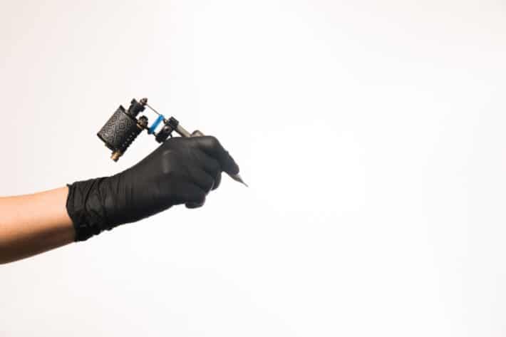 Reka tatuazysty trzymająca maszynkę do tatuażu, która zrobi tatuaż mapa świata