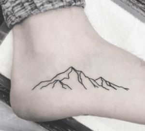Tatuaż góry na stopie