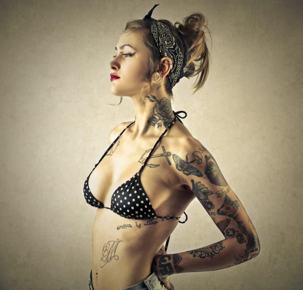 Młoda kobieta w tatuażam, w tym także w tatuażu na obojczyku