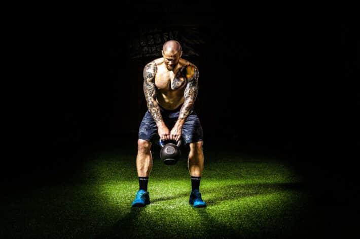 Mężczyzna w tatuażach ćwiczący na siłowni