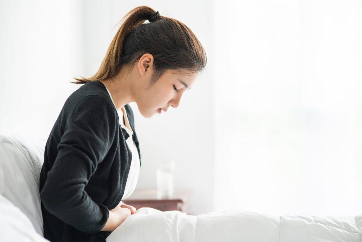 Młoda kobieta leżąca w łóżku i myśląca nad tym, czy w czasie okresu można zajść w ciążę
