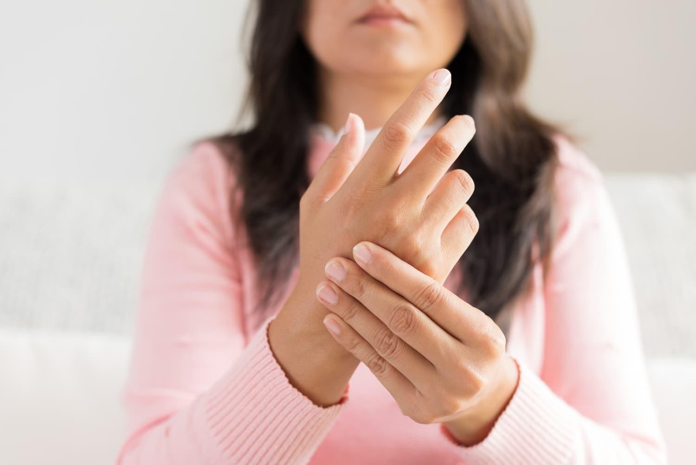 Młoda kobieta w różowym sweterku odczuwająca drętwienie prawej ręki
