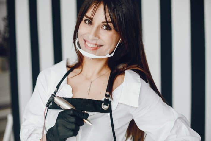 Kobieta z maszynką do robienia tatuaży w ręku