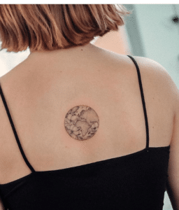 Krótko ścięta kobieta z tatuażem świat na plecach