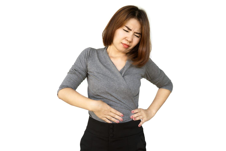 Kobieta odczuwająca ból z lewej strony pod żebrami