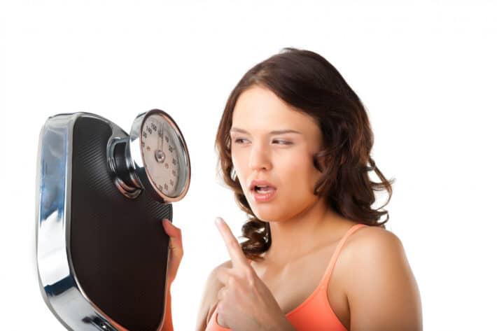 Kobieta na diecie z waga w ręku która za wszelką cenę pragnie uniknąć efektu jojo