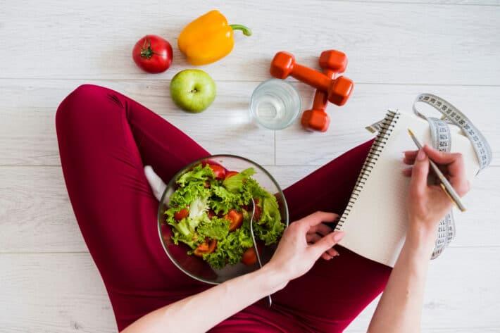 Kobieta wypisująca w notesie, ile kalorii potrzebuje organizm do funkcjonowania