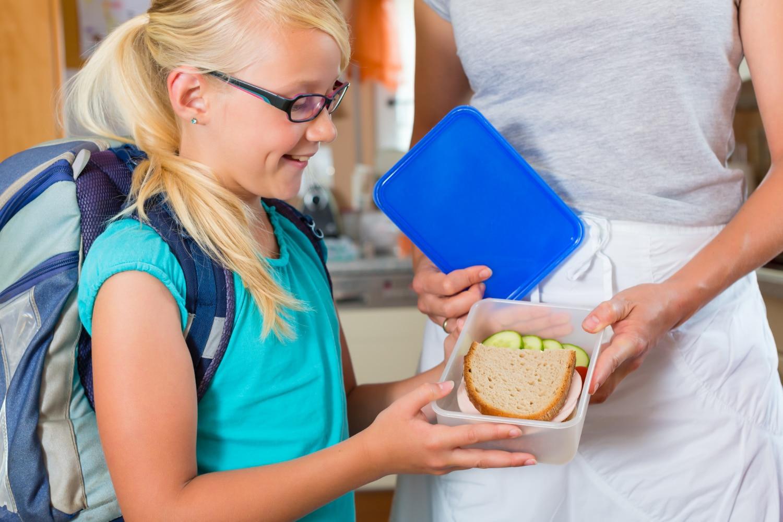 Dziewczynka ucieszona na widok kanapek do szkoły
