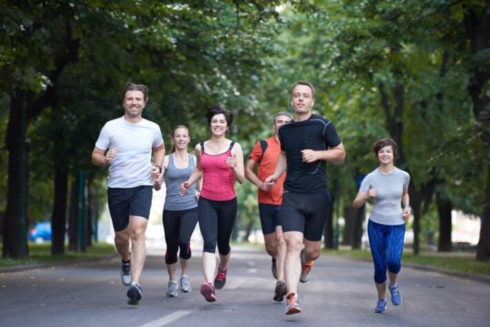 Grupa osób biega po parku.