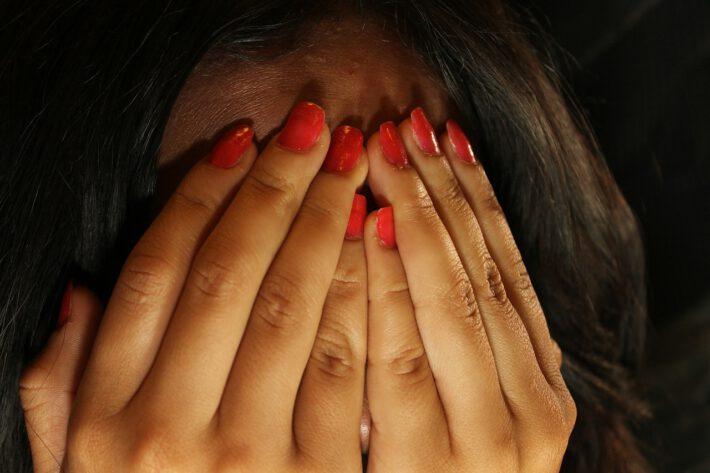 Kbieta zasłania twarz dłońmi ze wstydu
