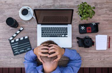 Mężczyzna przy laptopie trzyma się za głowe