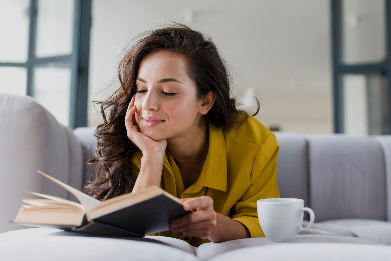 Kobieta z usmiechem na twarzy czytająca książki
