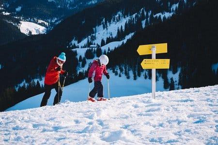dziecko z tatą jeździ na nartach