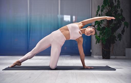 Kobieta ćwiczy na macie w domu