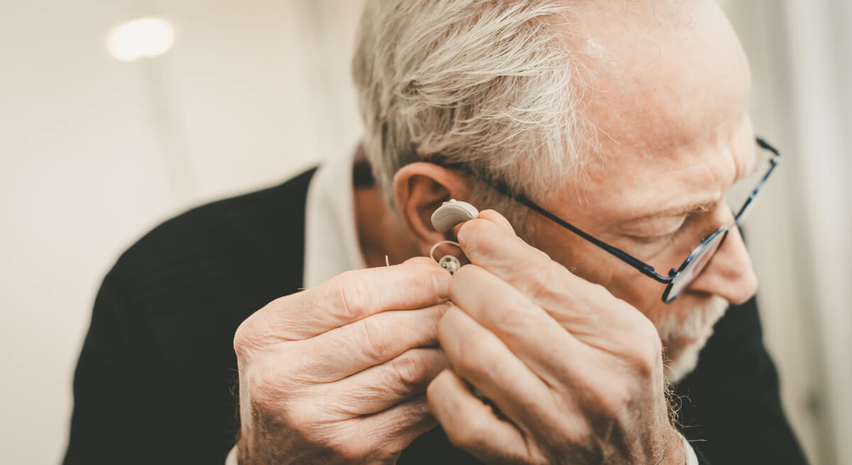 Starszy mężczyzna zakłada aparat słuchowy